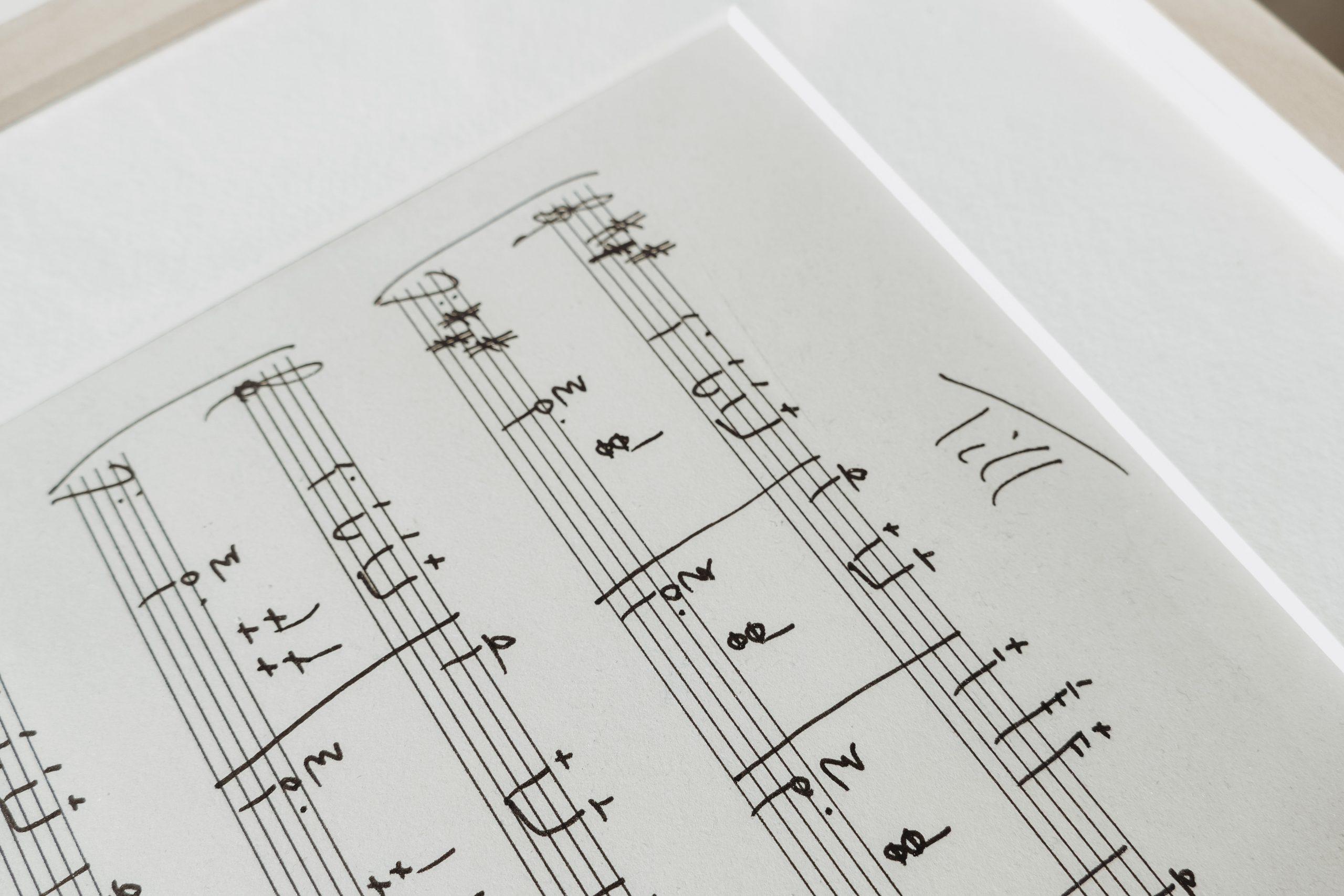 Eine Detailaufnahme eines Bilderrahmens mit handgeschriebenen Noten darin